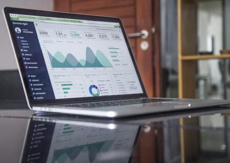 Laptop auf Arbeitsplatz mit Analyse Dashboard